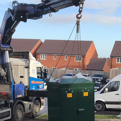 Crane Lifting EV charging enclosures onto installation site